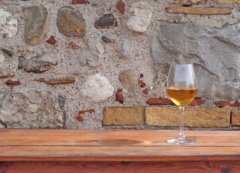 Glas amber witte wijn op een rustieke houten lijst met een oude steen erachter muur achtergrond voor exemplaarruimte royalty-vrije stock afbeelding