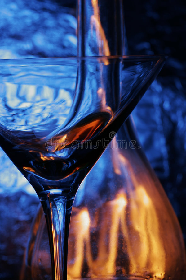 Glas & fles over blauwe backg stock afbeeldingen