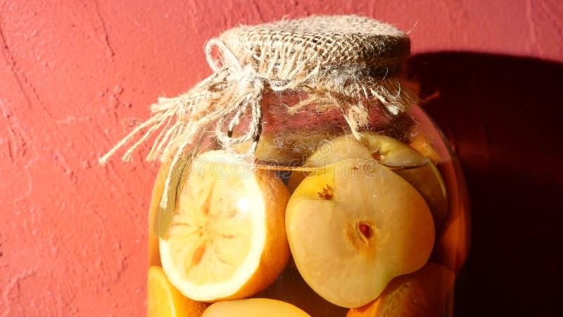 Glas Apfel- und Zitronenkompott auf einem roten Hintergrund stockfotos