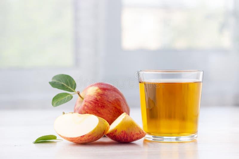 Glas appelsap en rijpe rode appelen met bladeren royalty-vrije stock foto's