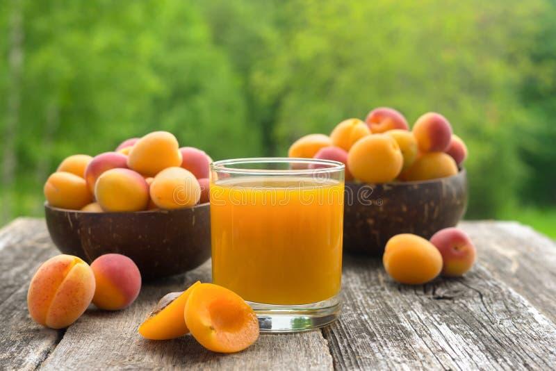 Glas Aprikosensaft und frische Aprikosen auf Holztisch mit grünem Hintergrund lizenzfreie stockfotos
