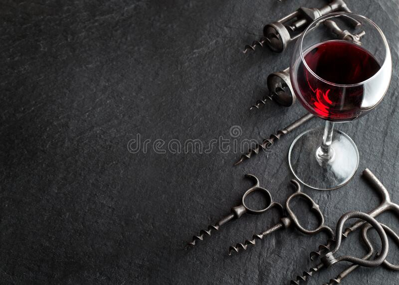 Glas aus Rotwein und Korkschrauben auf dunklem Hintergrund Glas aus Rotwein und Korkschrauben auf dunklem Hintergrund stockfotografie