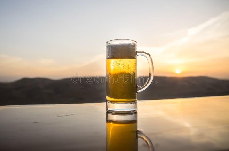 Glas Bier auf einem Strand bei Sonnenuntergang Abkühlendes Sommergetränkkonzept Schließen Sie oben von einem Glas Fassbier mit de lizenzfreies stockbild