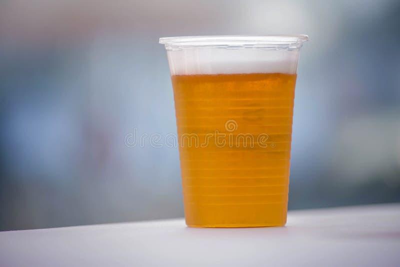 Glas bier in een plastic kop stock foto