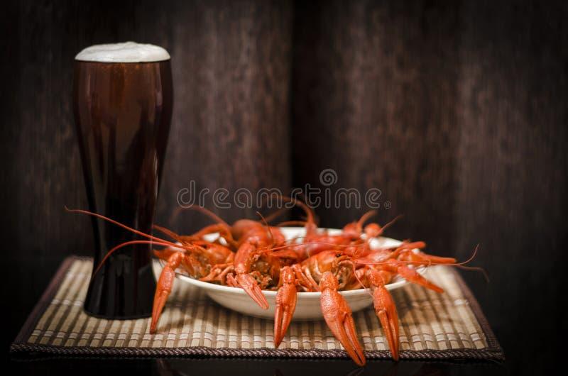 Glas bier en een plaat van gekookte rivierkreeften op een lijst royalty-vrije stock foto's