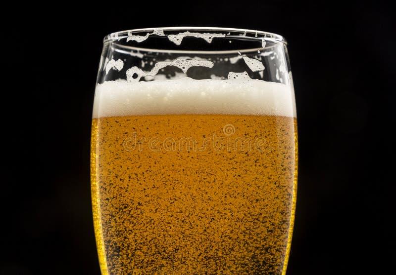 Glas bier met bellen en schuim op zwarte close-up stock afbeeldingen