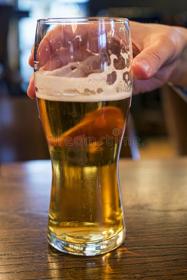 Glas bier met een hand stock fotografie