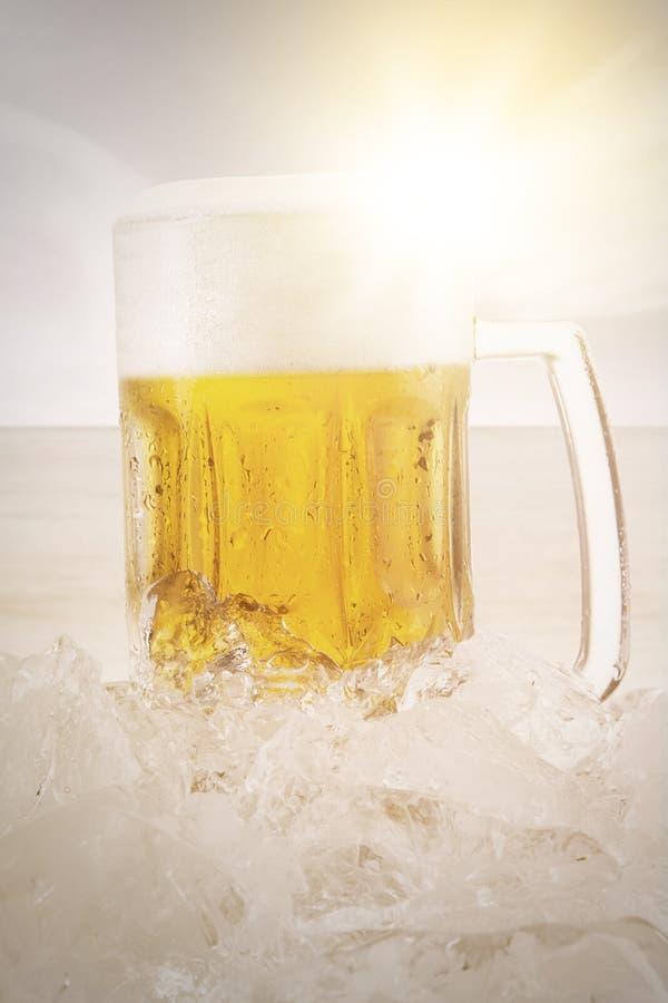 Glas bier met schuim en ijsblokje royalty-vrije stock foto's
