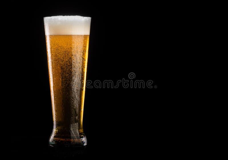 Glas bier met schuim op zwarte achtergrond stock afbeelding