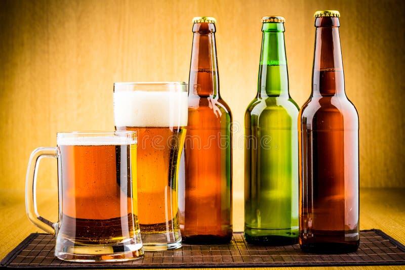Glas Bier mit Flaschen lizenzfreies stockbild