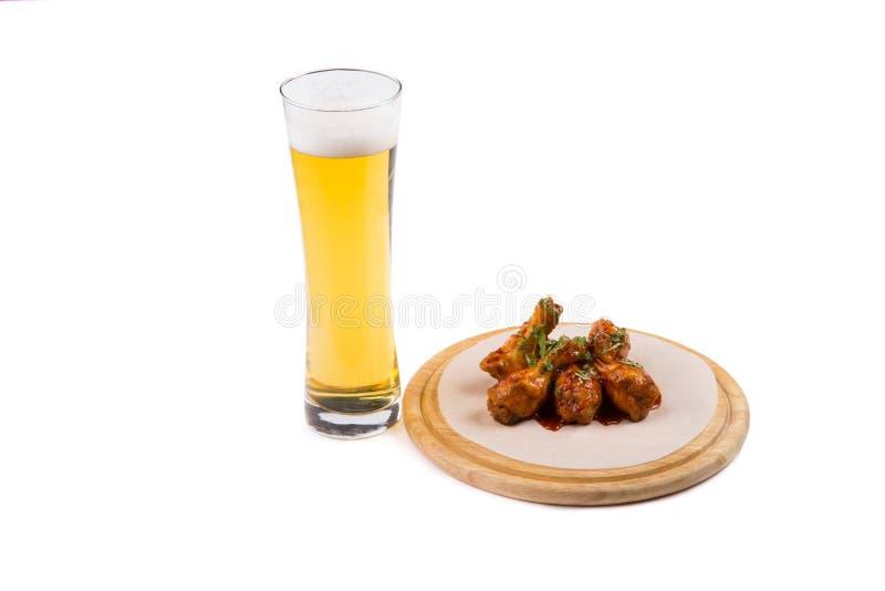 Glas Bier mit Hühnerflügeln lizenzfreie stockbilder