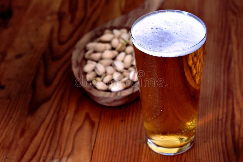 Glas Bier mit Pistazie stockfotos