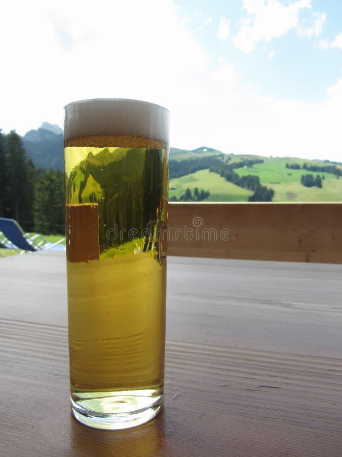 Glas bier op de lijst aangaande berg vage achtergrond royalty-vrije stock foto's