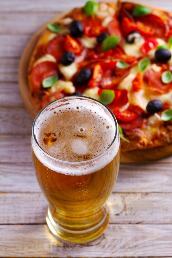 Glas Bier und Pizza auf Holztisch Bier- und Lebensmittelkonzept ale stockfotos