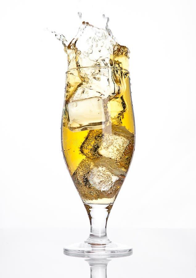 Glas biercider met ijsblokjeplons op wit royalty-vrije stock foto