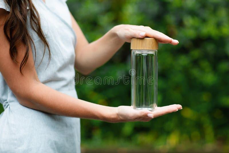 Glas bootle in vrouwenhanden royalty-vrije stock fotografie
