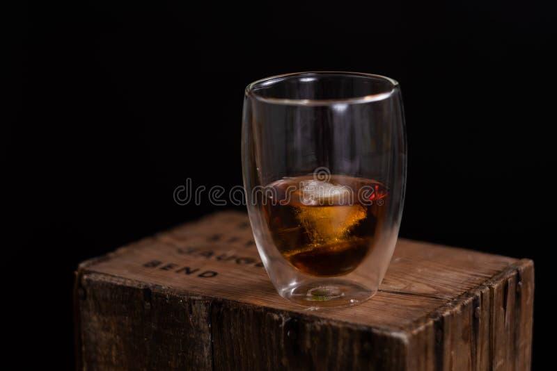 Glas bourbon op houten doos royalty-vrije stock fotografie