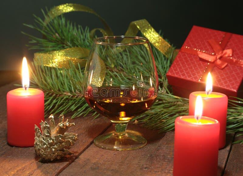 Glas brandewijn of cognac, giftvakje en kaars op de houten lijst Vieringssamenstelling royalty-vrije stock fotografie