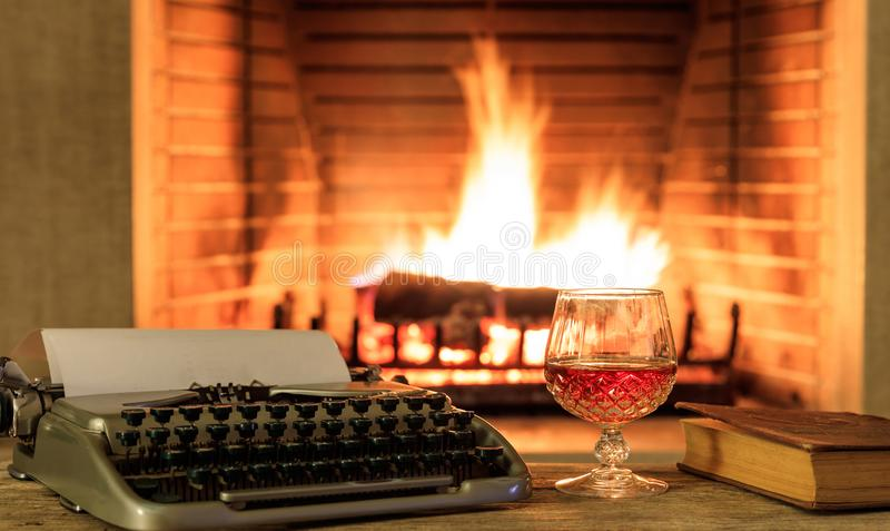 Glas brandewijn en een schrijfmachine bij het branden van open haardachtergrond stock foto