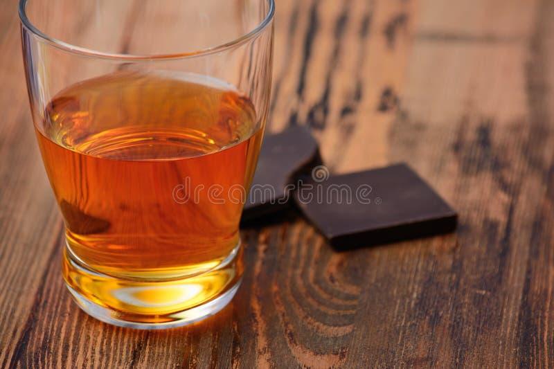 Glas brandewijn, wisky, cognac op een houten tafelblad met chocoladerepen royalty-vrije stock fotografie