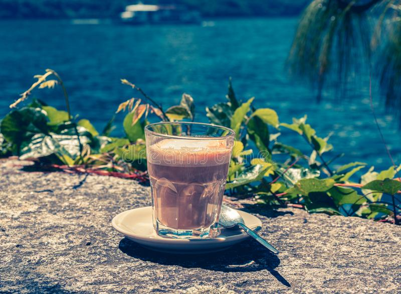 Glas of cafe latte on a stone wall with water in the background royalty free stock photography
