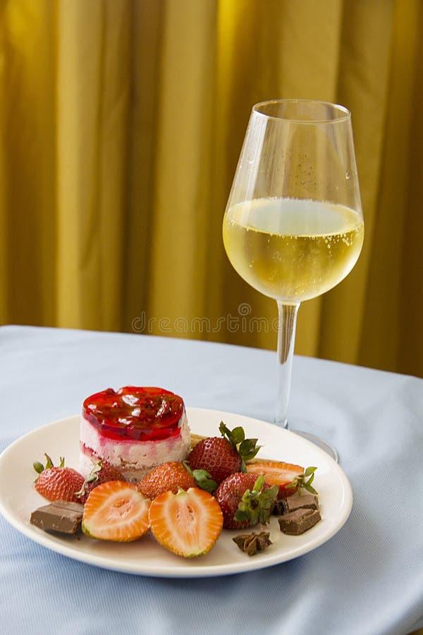 Glas champagne met aardbeien op gouden achtergrond royalty-vrije stock afbeelding