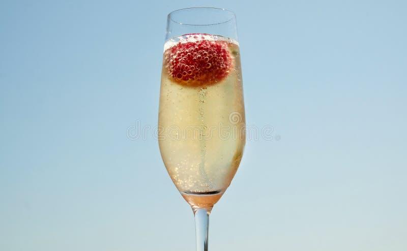 Glas Champagner mit einer Erdbeere, die in ihr sprudelt stockbild