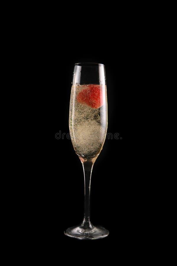 Glas Champagner mit Erdbeere stockfotos