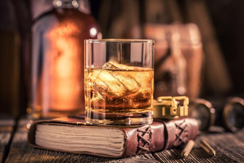 Glas cognac met ijs en gouden fles royalty-vrije stock foto's