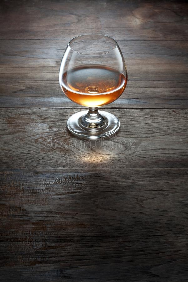 Glas cognac op de bruine oppervlakte van de kleuren houten lijst stock foto's