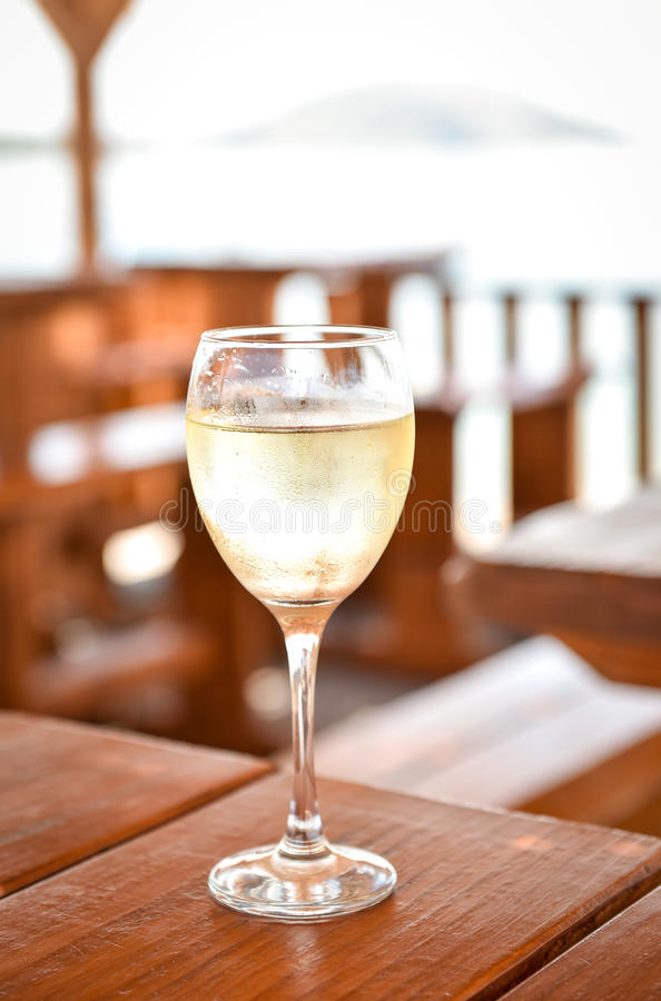 Glas of cold white wine on a wooden table. Glass of cold white wine on a wooden table. Refreshing drink on the beach hut on vacation. Ice cold beverage with royalty free stock photo