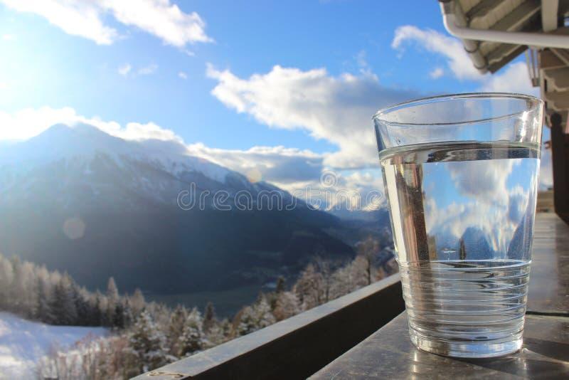 Glas de l'eau minérale sur la balustrade avec le paysage de montagne et le ciel nuageux bleu image stock