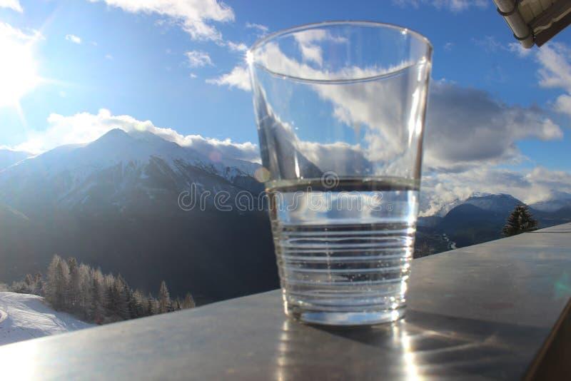 Glas de l'eau minérale sur la balustrade avec le paysage de montagne et le ciel nuageux bleu photo libre de droits
