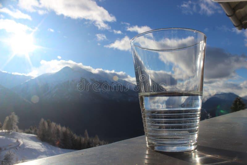 Glas de l'eau minérale sur la balustrade avec le paysage de montagne et le ciel nuageux bleu images stock