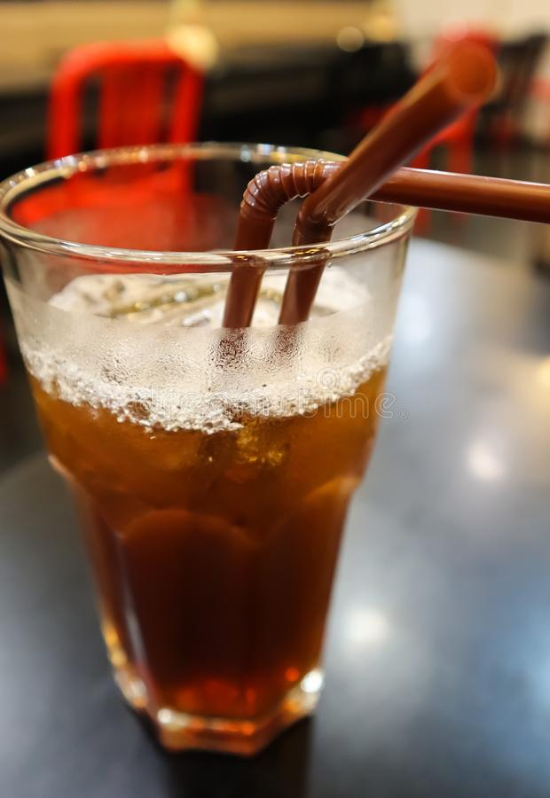 Glas de thee van de ijscitroen met twee bruin stro op de zwarte lijst in het restaurant Één glas voor twee, samen Het beeld van h stock foto's