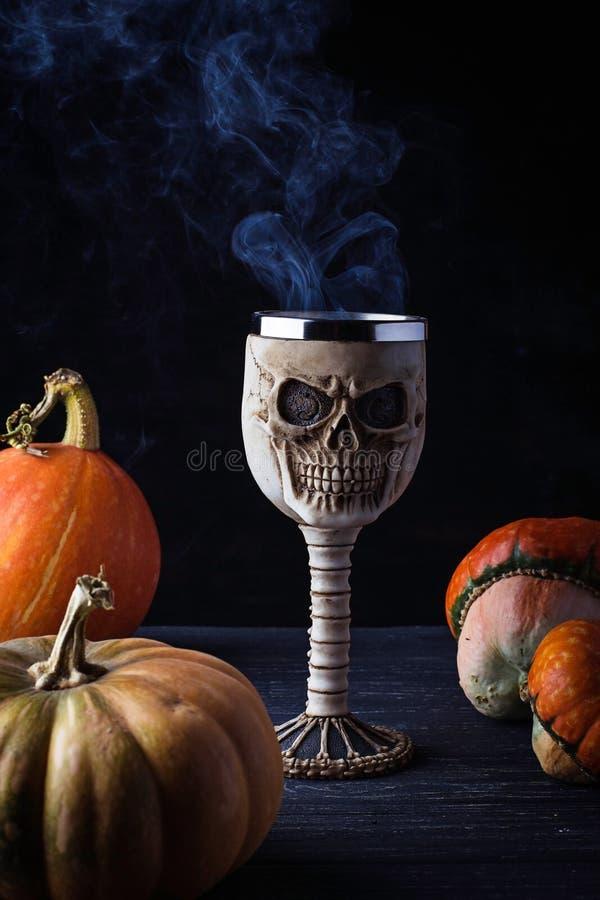 Glas in der Form ein Schädel mit Halloween-Getränk lizenzfreie stockfotografie