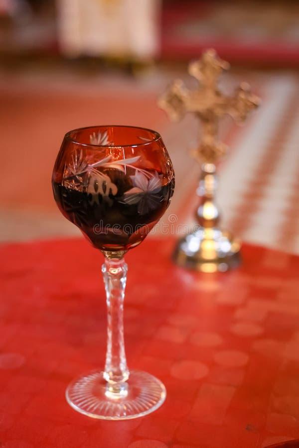 Glas der Rebe im vorderen und unscharfen Hochzeitszeremoniekreuz im Hintergrund Orthodoxe Zusätze der kirchlichen Hochzeit stockfotografie