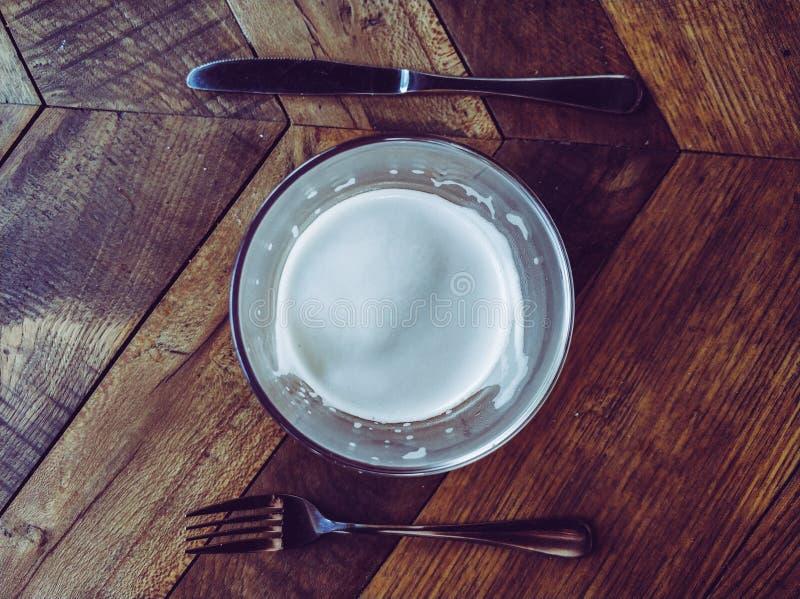 Glas des Bieres, der Gabel und des Messers auf Holztisch stockfoto