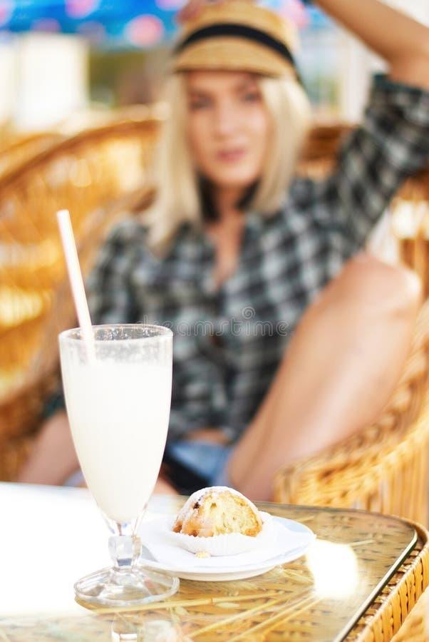 Glas des Cocktails und des Muffins auf einer Tabelle stockfoto