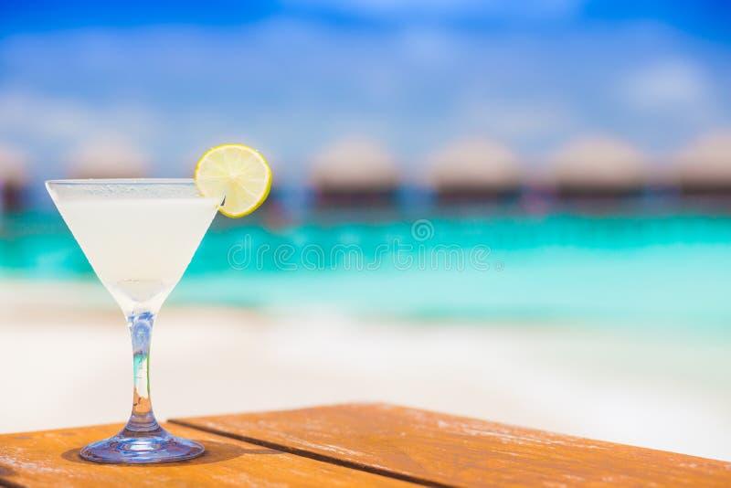 Glas des Daiquiricocktails mit Kirsche durch den Strand stockbilder
