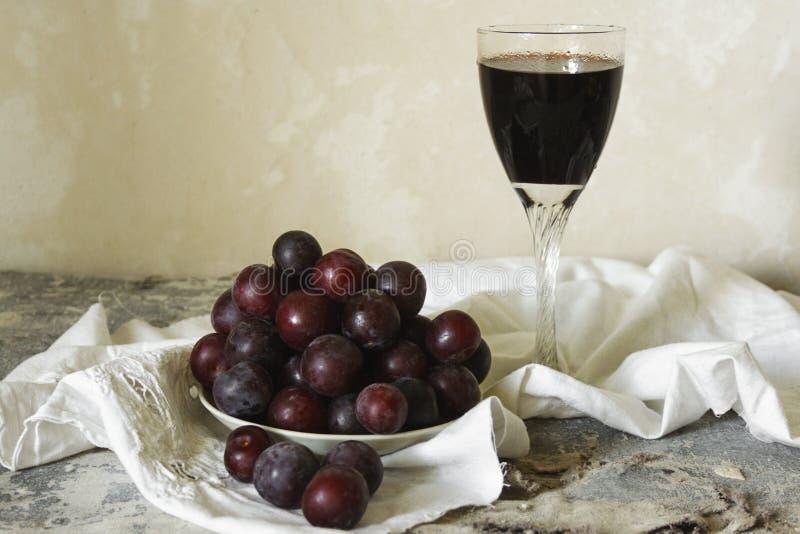 Glas des Dessertweins und der Platte der frischen Pflaumen auf einem hellen Hintergrund in der rustikalen Art lizenzfreie stockfotografie