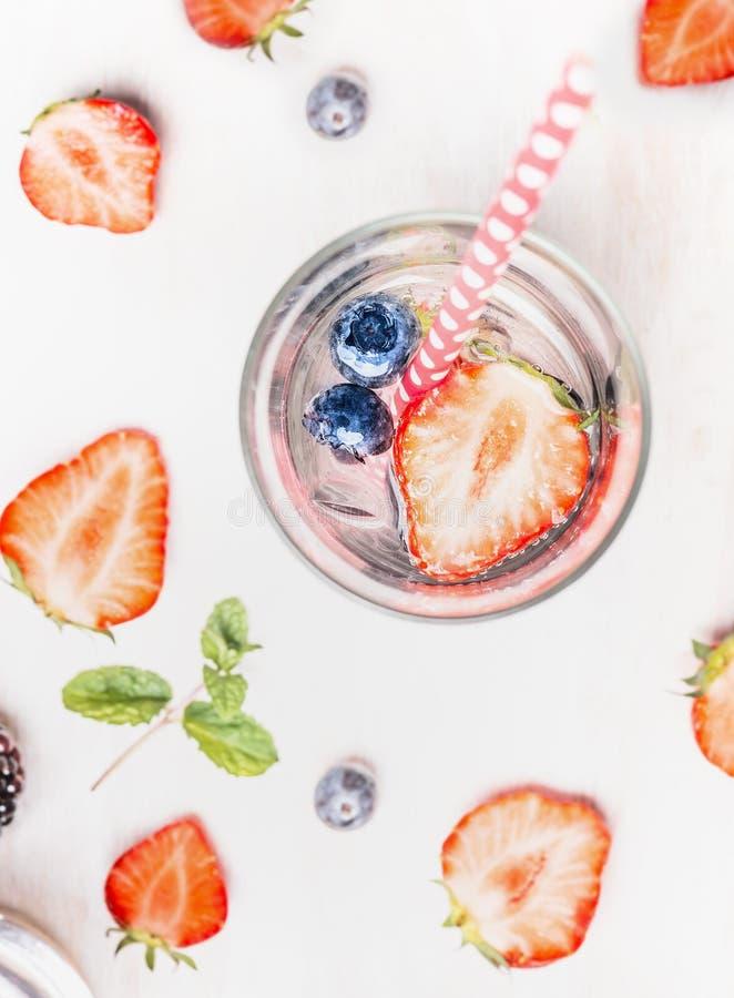 Glas des Detoxgetränks mit hineingegossenem Wasser, frischen Beeren, Eiswürfeln und tadellosen Blättern stockfoto