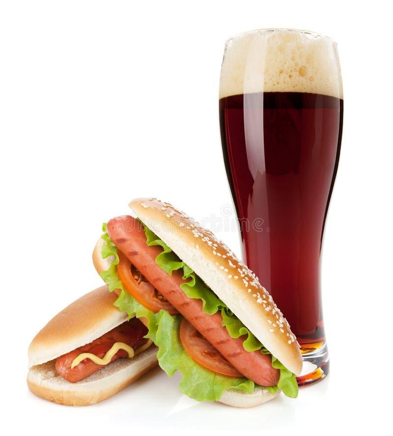 Glas des dunklen Bieres und zwei Würstchen mit verschiedenen Bestandteilen lizenzfreies stockfoto