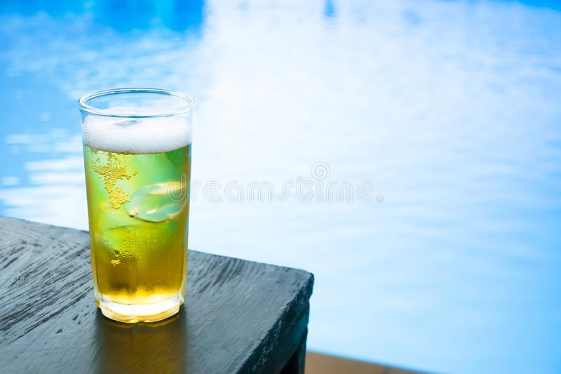 Glas des hellen Bieres auf dem Holztisch am Pool lizenzfreies stockfoto