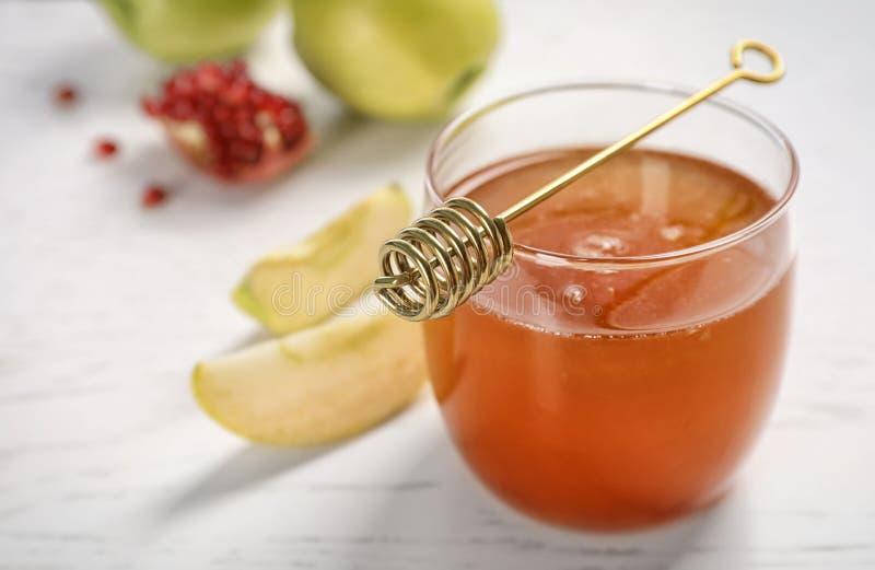 Glas des Honigs, der Äpfel, des Granatapfels und des Schöpflöffels stockfotografie