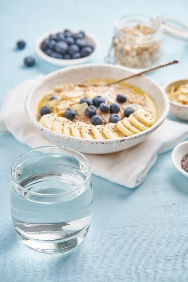 Glas des klaren Wassers und des Frühstücks der gesunden Diät mit Hafermehl, Blaubeeren, Banane auf Blaulichthintergrund vertikal  lizenzfreie stockbilder