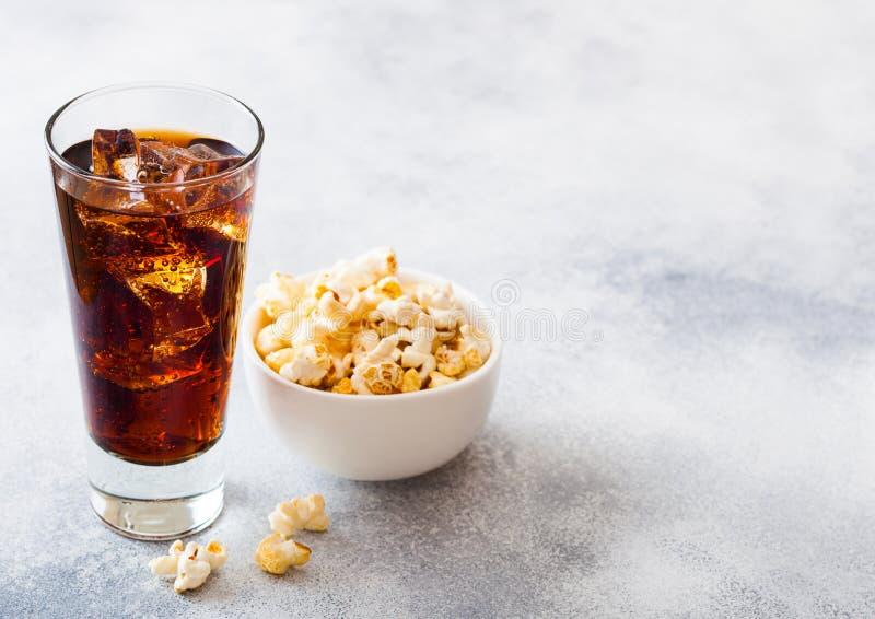 Glas des Kolabaumsodagetränks mit Eiswürfeln und weißer Schüssel des Popcornsnacks auf Steinküchentischhintergrund stockfotos