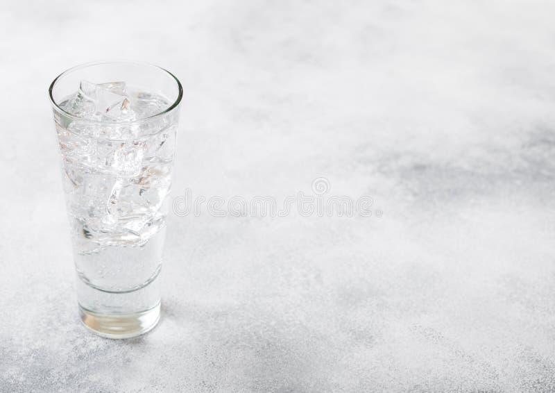 Glas des Limonadengetränks des funkelnden Wassers mit Eiswürfeln und -blasen auf Steinküchentischhintergrund stockbilder