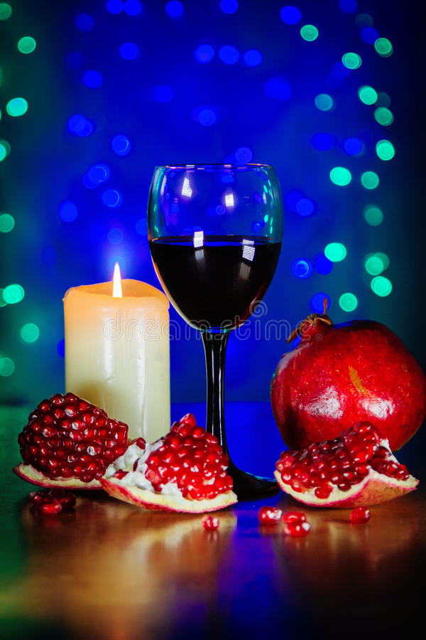 Glas des Rotweins, des reifen Granatapfels und der brennenden Kerze lizenzfreie stockfotografie
