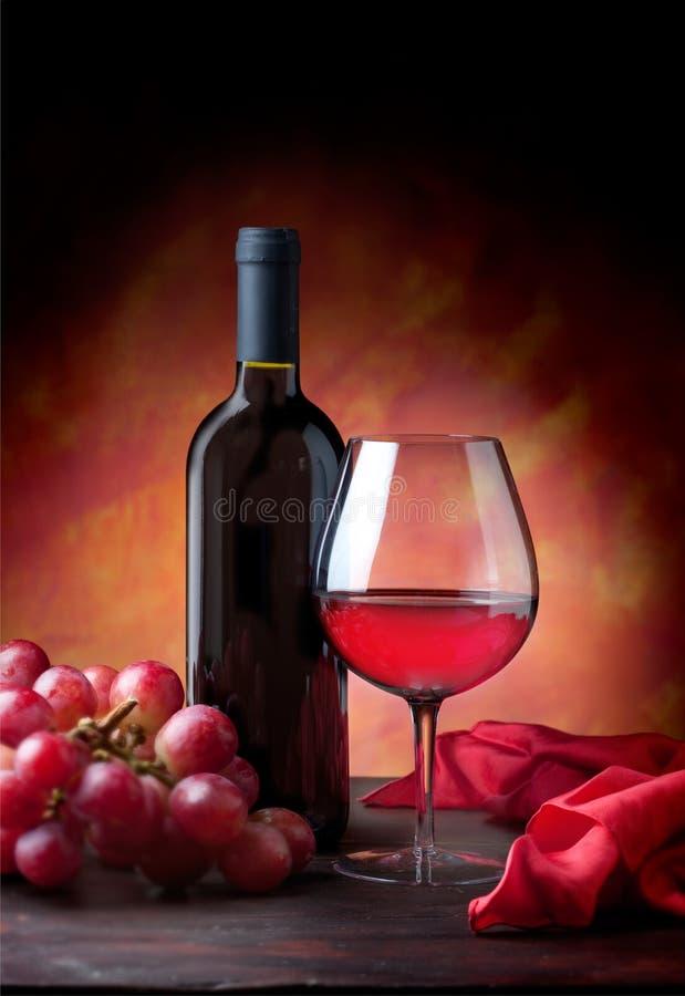Glas des Rotweins und der Flasche mit Trauben stockbilder